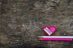 Herz-förmiger rosa Bleistiftspitzer und zwei Bleistifte Stockfotografie
