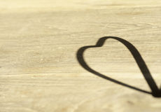 Herz-förmiger Schatten auf dem Bretterboden Stockbild