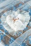 Herz-förmiges Kissen mit Chiffon- Spitze- und Hochzeitsgoldringen Stockfoto