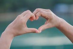Herz-förmiges menschliches Herz auf einem unscharfen Hintergrund Die Leistung der Liebe Lizenzfreie Stockfotos