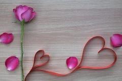 Herz-Formband mit zwei Rottönen mit Rosarose und -blumenblättern auf Holzoberfläche mit Raum für Text Lizenzfreies Stockbild