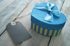 Herz formte die Geschenkbox, die mit einem blauen Band und einem Aufkleber verziert wurde Lizenzfreies Stockfoto