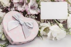 Herz formte Geschenkbox und Blumen mit einem Namensschild Lizenzfreie Stockfotos