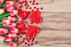 Herz formte Lutscher auf dem hölzernen Hintergrund, gezeichnet mit Tulpenblumen Festlicher Hintergrund zum Valentinstag lizenzfreies stockbild