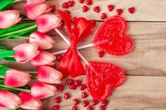 Herz formte Lutscher auf dem hölzernen Hintergrund, gezeichnet mit Tulpenblumen Festlicher Hintergrund zum Valentinstag stockfoto