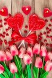 Herz formte Lutscher auf hölzernem Hintergrund mit Herzen formte die Kerzen, die mit Tulpenblumen gezeichnet wurden Festlicher Hi stockfotografie