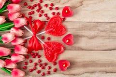 Herz formte Lutscher auf hölzernem Hintergrund mit Herzen formte die Kerzen, die mit Tulpenblumen gezeichnet wurden Festlicher Hi stockfotos