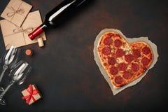 Herz formte Pizza mit dem Mozzarella, sausagered, Weinflasche, zwei Weinglas, Geschenkbox auf rostigem Hintergrund stockbild
