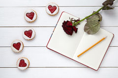 Herz formte Plätzchen mit leerem Notizbuch, Bleistift und rosafarbener Blume auf weißem hölzernem Hintergrund für Valentinsgrußta Stockfotos