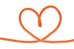 Herz formte roten Knoten auf einem Jutefaserseil, das auf Weiß lokalisiert wurde Stockfotos