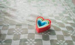 Herz formte Schüssel auf einem grünen Stoffhintergrund Stockbilder