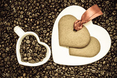 Herz formte Schale und Plätzchen auf Kaffeebohnehintergrund Lizenzfreies Stockfoto