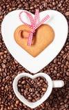 Herz formte Schale und Plätzchen auf Kaffeebohnehintergrund Stockfotografie