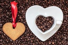 Herz formte Schale und Plätzchen auf Kaffeebohnehintergrund Stockbilder