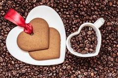 Herz formte Schale und Plätzchen auf Kaffeebohnehintergrund Lizenzfreie Stockfotos