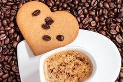 Herz formte Schale und Plätzchen auf Kaffeebohnehintergrund Lizenzfreie Stockbilder