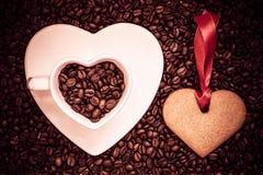 Herz formte Schale und Plätzchen auf Kaffeebohnehintergrund Stockbild