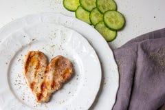 Herz formte Scheibe des Fleisches an der doppelten Platte am weißen Hintergrund Stockfotografie
