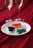 Herz formte Toast mit rotem und schwarzem Kaviar und zwei Gläsern Champagner auf weißer Platte auf rotem Drapierung Lizenzfreies Stockfoto