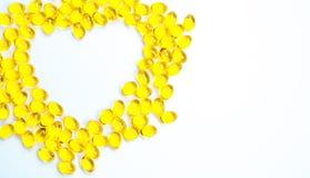 Herz formte vom Lebertran, der auf weißem Hintergrund mit Kopienraum lokalisiert wurde Quelle von Omega-3 DHA+EPA und Vitamin A u lizenzfreie stockfotos
