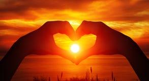 Herz formte weibliches Handschattenbild mit Sonnenunterganghintergrund stockbilder