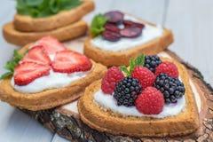 Herz geformte Kekse verbreiteten mit Quark, Erdbeeren, blackberr Lizenzfreie Stockbilder