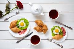 Herz geformte Spiegeleier, Salat, Hörnchen, Salamiwurst, rosafarbene Blumenzusammensetzung und Tee, weißer Holztisch Stockbild