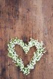 Herz geformter Blumenkranz auf rustikalem Hintergrund Stockbilder