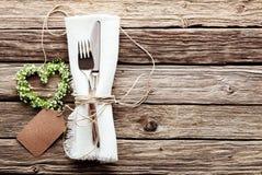 Herz geformter Hochzeits-Kranz am rustikalen Gedeck