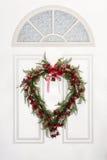 Herz geformter Kranz, der an der weißen Tür hängt Lizenzfreies Stockbild