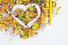 Herz, gelber Bleistift und hölzerne Chips Stockfoto