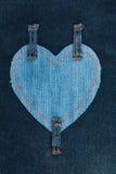 Herz gemacht vom Denimgewebe und drei Bügeln auf Dunkelheit befestigt Stockbilder