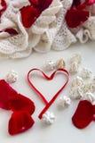 Herz gemacht vom roten Band mit Meringe Stockfotos