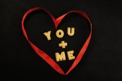 Herz gemacht vom roten Band mit Wörtern Sie + ich nach innen Lizenzfreies Stockfoto