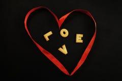 Herz gemacht vom roten Band mit Wortliebe nach innen Lizenzfreies Stockbild