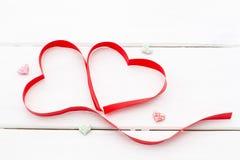 Herz gemacht vom roten Band und von einigen wenig Herzen auf weißem hölzernem Hintergrund Stockbilder