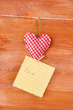 Herz gemacht vom Stoff mit einer Anmerkung auf hölzernem Hintergrund Lizenzfreie Stockbilder