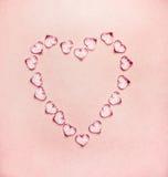 Herz gemacht von den Glasherzen auf blassem - rosa Hintergrund lizenzfreie stockbilder