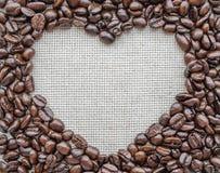 Herz gemacht von den Kaffeebohnen auf strukturiertem Sack Lizenzfreie Stockfotos