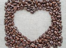 Herz gemacht von den Kaffeebohnen auf strukturiertem Sack Stockbilder