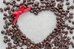 Herz gemacht von den Kaffeebohnen auf strukturiertem Sack Stockfotos