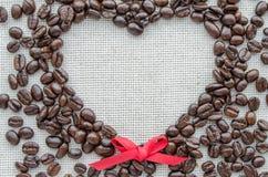 Herz gemacht von den Kaffeebohnen auf strukturiertem Sack Lizenzfreies Stockbild