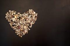 Herz gemacht von den kleinen glatten Kiessteinen stockfotos