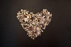Herz gemacht von den kleinen Steinen des ruhigen Sees lizenzfreies stockbild