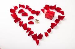 Herz gemacht von den roten rosafarbenen Blumenblättern und vom goldenen Ring Lizenzfreie Stockfotos