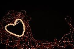Herz gemacht von den weißen und roten Perlen Lizenzfreie Stockbilder