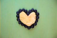 Herz gemacht von der gelben Ananas und von der frischen Blaubeere stockfotos