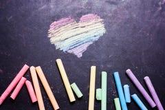 Herz gemalt mit Regenbogen-farbiger Kreide auf einer Tafel stockbilder