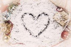 Herz gezeichnet auf den Schnee mit Geschenken Lizenzfreies Stockbild