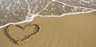 Herz gezeichnet auf Ozeanstrandsand romantisch Lizenzfreie Stockfotografie